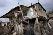 An ethnic Armenian man walks past a destroyed house during the fighting in Martakert province of Nagorno-Karabagh, Monday, April 4, 2016 (Photo by Vahan Stepanyan/PAN Photo via AP Photo)